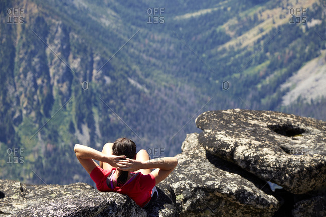Hiker sitting on rocky hilltop, Leavenworth, Washington, USA