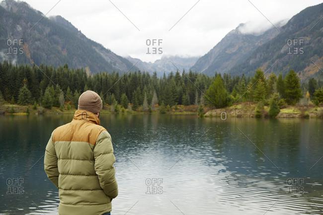Hiker admiring lake and remote landscape, North Bend, Washington, USA