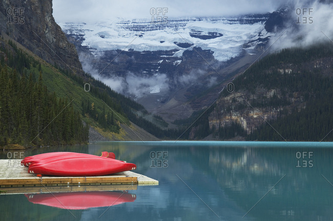 April 10, 2019: Canoes on wooden dock over still remote lake, Banff, Alberta, Canada
