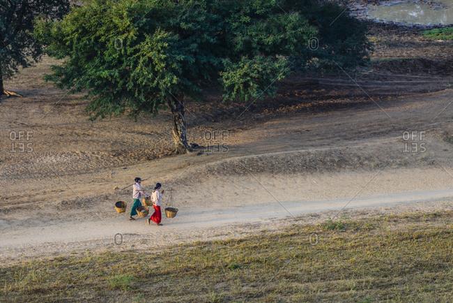 People carrying baskets on dirt path in rural landscape, Myanmar, Burma
