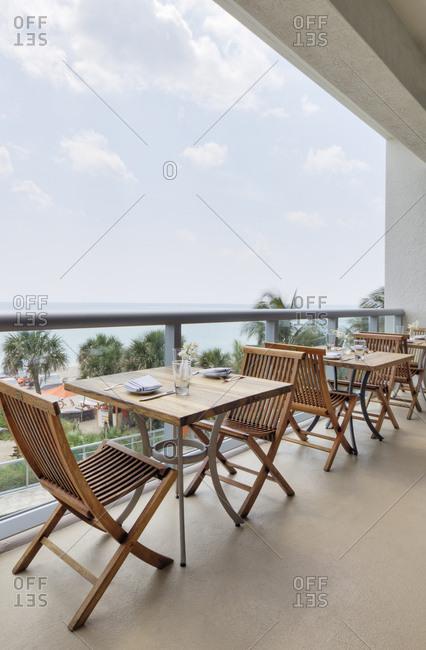 April 10, 2019: Empty tables on restaurant balcony, Miami, Florida, USA