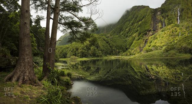 Still lake under remote mountains, Faja Grande, Flores, Portugal
