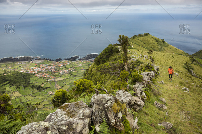 Hiker walking on hilltop path in rural landscape, Faja Grande, Flores, Portugal