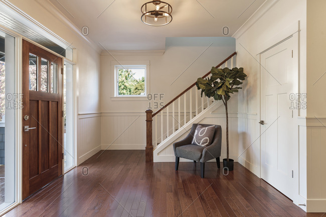 Armchair and tree in house entryway, Lake Oswego, Oregon, USA