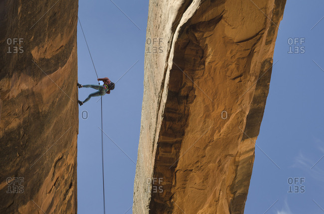 Rock climber using rope on arch, Moab, Utah, USA
