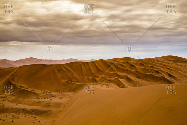 Red sand dunes in the Namib desert under a cloudy sky, Namib-Naukluft National Park; Sossusvlei, Hardap Region, Namibia