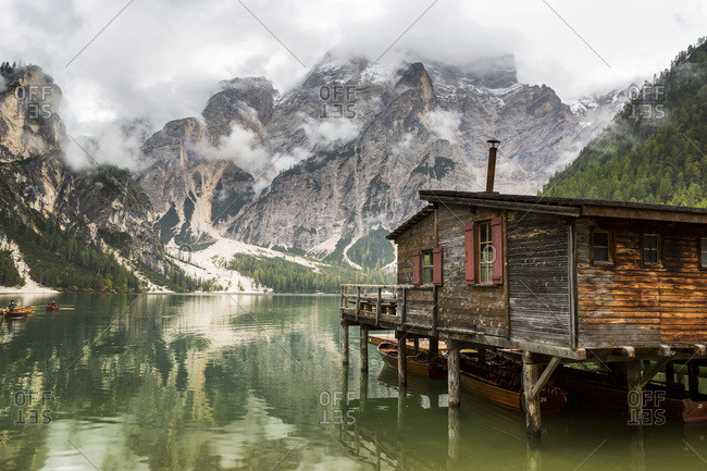 Wooden lake boat house with misty clouded mountain in the background and lake reflection; Sesto, Bolzano, Italy