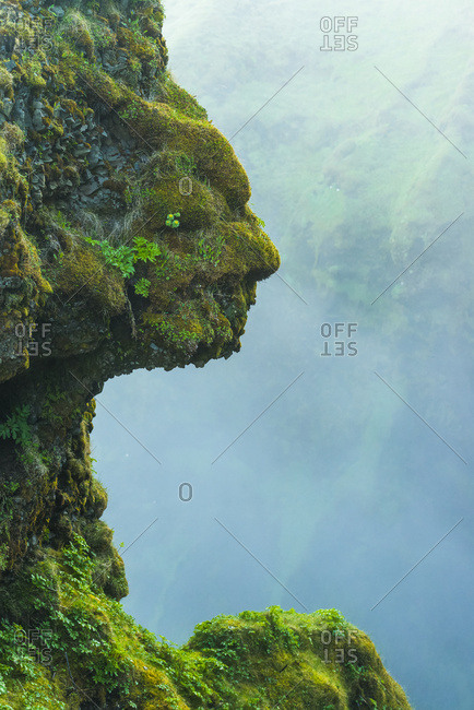 Shape of head in natural rocks covered in green moss beside Skogafoss waterfall; Iceland