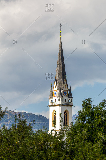 Elaborate church clock tower with trees in foreground and dark clouds in the background; Lienz, Tyrol, Austria
