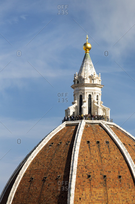 Close-up of Brunelleschi's Dome of Florence Cathedral with tourists on the viewing platform and blue sky; Florence, Tuscany, Italy