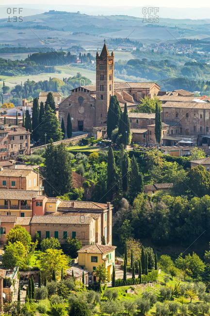 Stone buildings and church on landscape covered with trees and rolling hills in the background; Siena, Tuscany, Italy