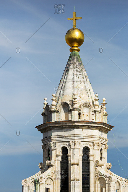 Close-up of the top of Florence Cathedral dome, with lantern, gold globe, and cross against a blue sky; Florence, Tuscany, Italy