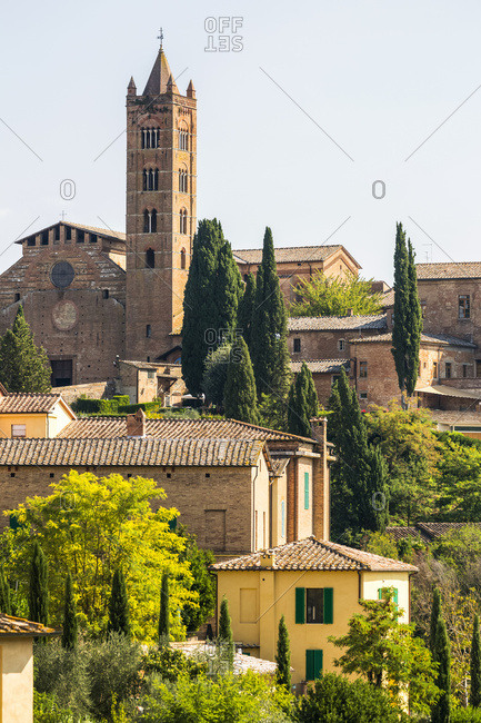 Stone buildings and church on landscape covered with trees; Siena, Tuscany, Italy
