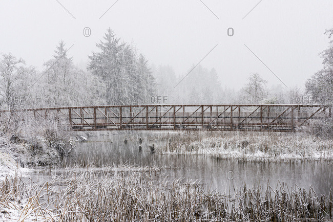 Snowfall enhances a rustic scene of a footbridge over a pond in Western Oregon; Astoria, Oregon, United States of America