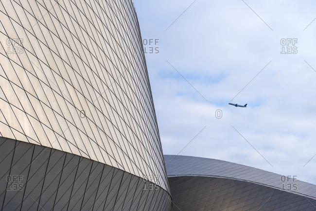 Plane taking off behind the Blue Planet Aquarium; Copenhagen, Denmark
