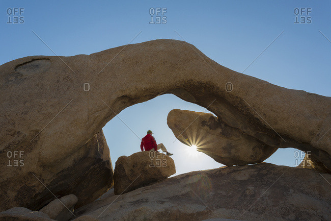 A hiker watching a sunrise under sandstone rock arch with sun star, Joshua Tree National Park; California, United States of America