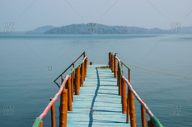 A dock leading out to the tranquil waters in the Bay of Bengal; Andaman Islands, India