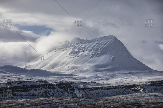 Snow covered peak behind the town of Djupavik; Djupavik, West Fjords, Iceland