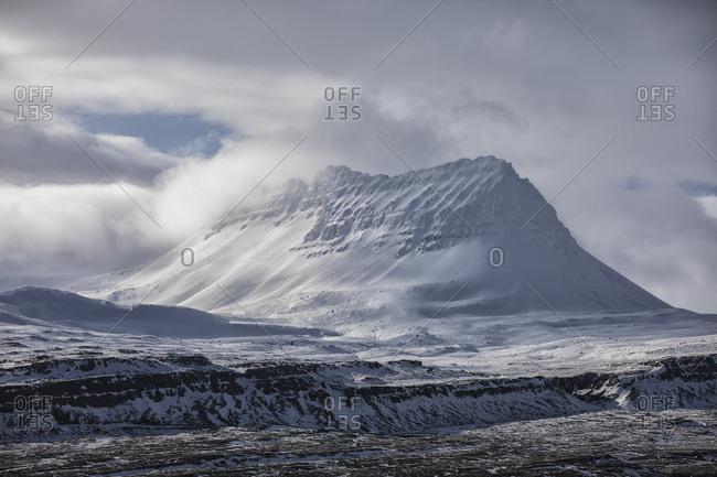 Snow covered peak behind the town of Djupavik; Djupavik, West Fjords, Iceland