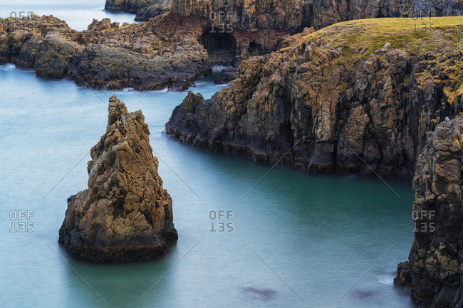 Amazing scenery along a remote section of the West Fjords with great autumn colours and a sea stack in the ocean; West Fjords, Iceland