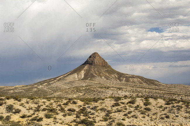 Interesting cone-shaped desert mountain under a stormy sky; Neuquen, Argentina