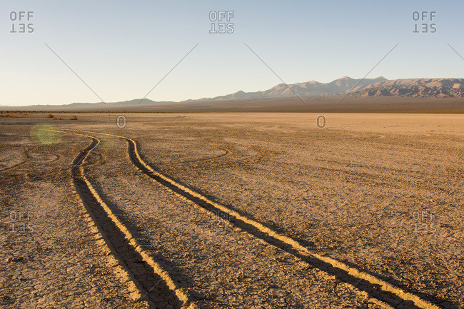 Tire tracks through a dry lake bed lead the eye to wards a mountain range at dawn; Barreal, San Juan, Argentina