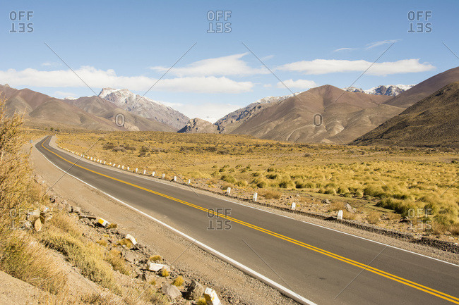 A road leads the eye through desert and snow-capped mountains; Malargue, Mendoza, Argentina