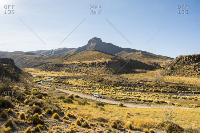 Wide view of a desert valley with interesting mountain in the distance. A road snakes through the valley with a white pickup truck parked on the side of the road in the center of the image; Malargue, Mendoza, Argentina