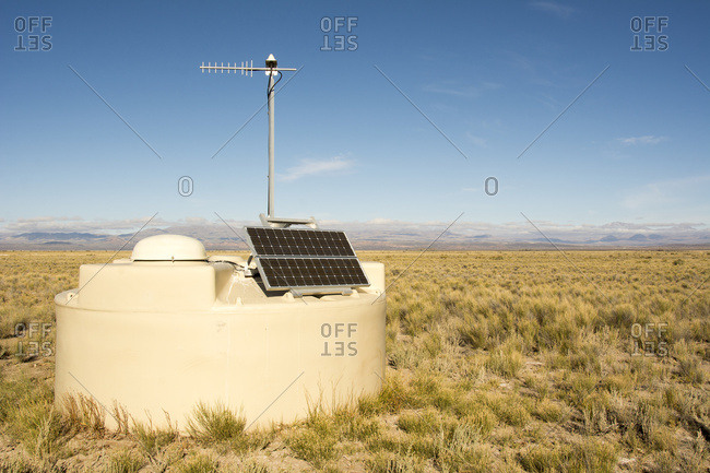 One of the detectors of the Pierre Auger observatory is seen close up with the Andes in the distance. The solar panel and antenna are clearly visible; Malargue, Mendoza, Argentina