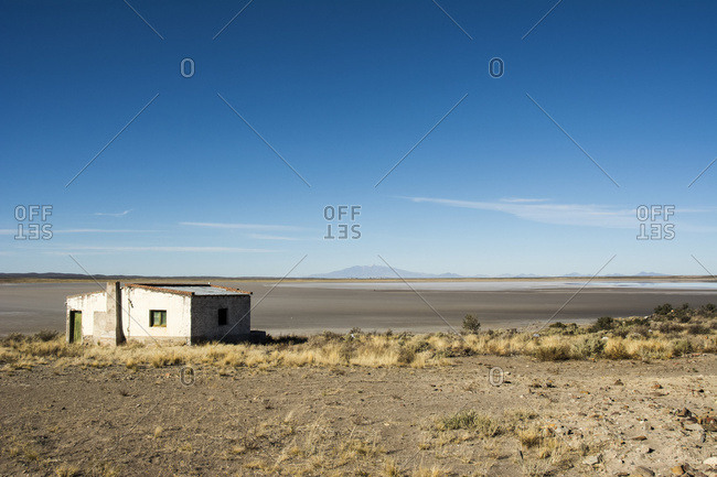 Wide view of a dry lake bed with a volcano in the distance. An abandoned white building is in the foreground; San Rafael, Mendoza, Argentina