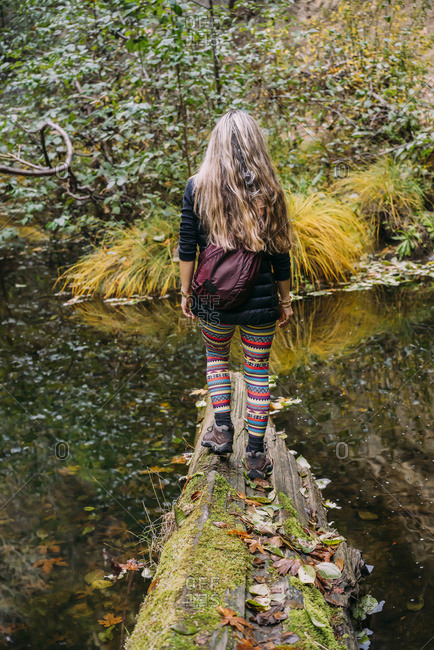 A woman walks across a log over a tranquil stream in autumn; California, United States of America