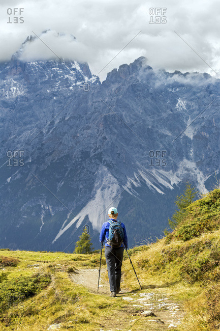 Female hiker along alpine trail with cloud covered mountains in the background; Sesto, Bolzano, Italy