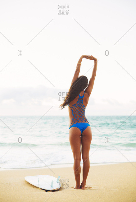 Beautiful Surfer Girl Stretching On The Beach. Summer Outdoor Lifestyle.