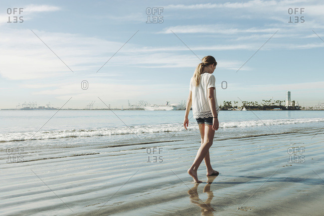 A girl walking on the beach on the wet sand; Long Beach, California, United States of America