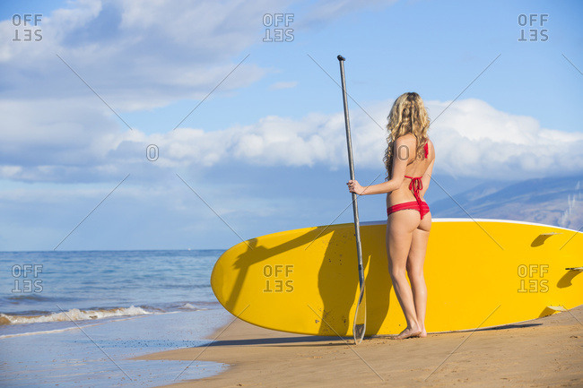 Young Attractive Woman On Stand Up Paddle Board, Sup, In The Blue Waters Off Hawaii