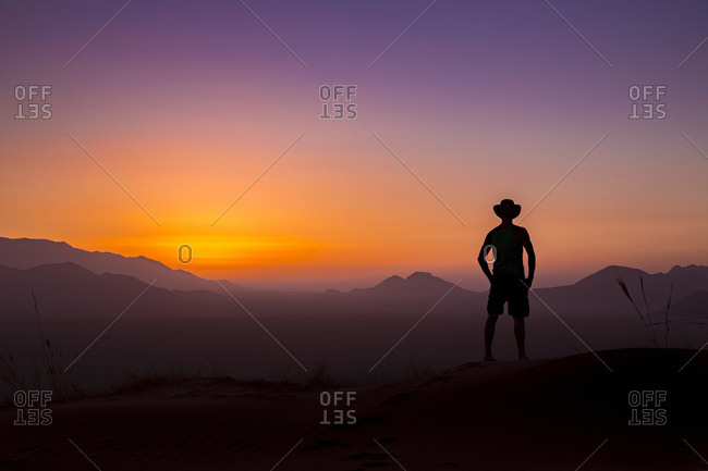Silhouette of a man wearing a cowboy hat stands looking out at the glowing landscape and sky at sunset; Sossusvlei, Hardap Region, Namibia