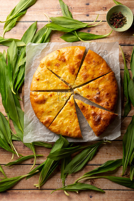 Overhead view of a flat bread with wild garlic on a wood table