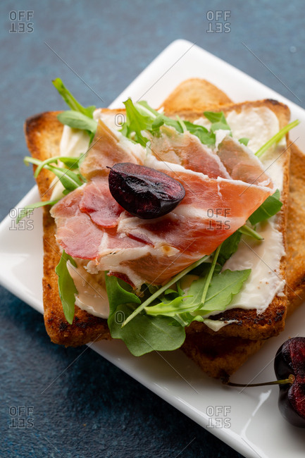 Appetizer toast with sliced prosciutto, greens, cheese, and black cherry