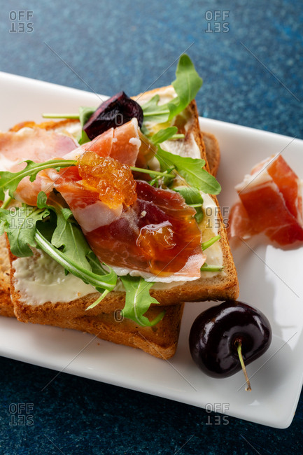 Toast with sliced prosciutto, greens and cheese