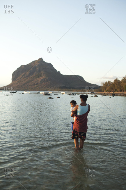 MAURITIUS,  - December 6, 2010: a mother and her child hunt for snails at low tide, Baie du Cap