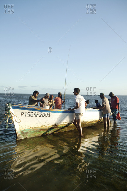 MAURITIUS,  - December 4, 2010: fishermen pull their rods and catch out of a boat after a day of fishing, Bel Ombre, Indian Ocean
