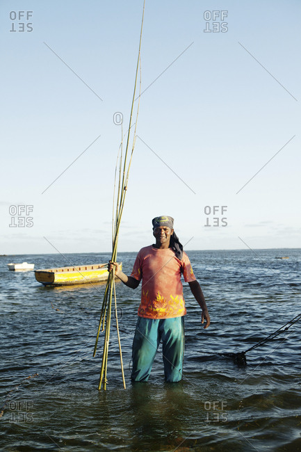 MAURITIUS,  - December 4, 2010: portrait of a fishermen with a bunch of handmade bamboo fishing rods, following a land day on the water, Bel Ombre, Indian Ocean
