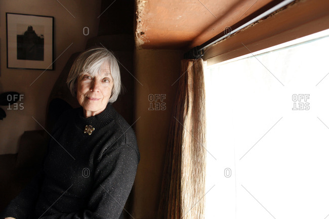 USA; New Mexico; Taos;  - December 19, 2011: The Mabel Dodge Luhan House, docent Judy Jordan sits by the fireplace
