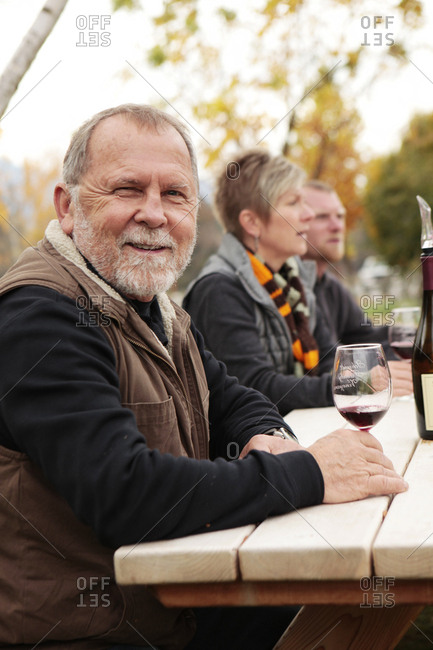 USA, Oregon, Medford, - November 2, 2012:  Cal Schmidt enjoys a glass of wine on his farm with friends, Schmidt Family Vineyards is located in the beautiful Applegate Valley and is owned by Judy and Cal Schmidt, the winery consists of country charm, beautiful gardens and fine wines