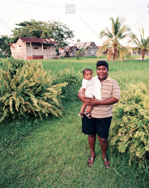 PANAMA, Bocas del Toro, - March 20, 2017:  a woman stands in her yard holding her daughter, Central America