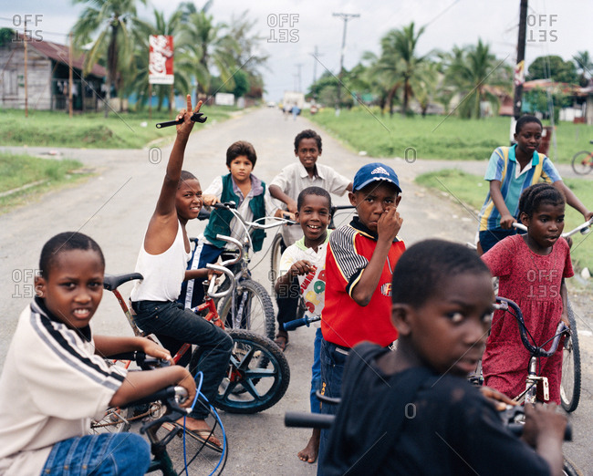 PANAMA, Bocas del Toro, - March 22, 2017:  kids on bikes hang in the street and wait to get access to the airport runway, Central America