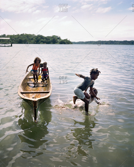PANAMA, Bocas del Toro, - March 20, 2017:  young kids jump out of a dugout canoe into Almirante Bay, Central America