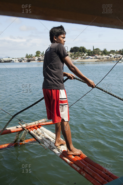 PHILIPPINES, Palawan, Puerto Princesa,  - February 6, 2011: PHILIPPINES, Palawan, Puerto Princessa, portrait of a fisherman in front of his boat in the City Port Area