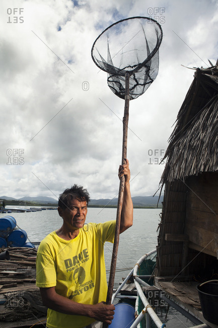 PHILIPPINES, Palawan, Puerto Princessa,  - February 6, 2011: fish farm employee Roberto Cabate in the Santa Lucia area