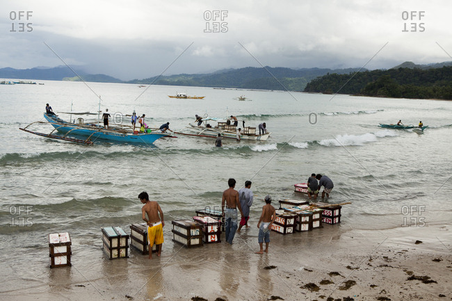 PHILIPPINES, Palawan, Sabang,  - February 8, 2011: boats drop supplies on the main beach in the town of Sabang